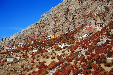 edifices: Overview of the mountain slope-caves-buildings-prayer flags on the way down from the main edifices of the Drak Yerpa monastery-complex of more than 80 buddhist meditation caves at 4885 ms.alt. Lhasa pref.-Tibet. Stock Photo