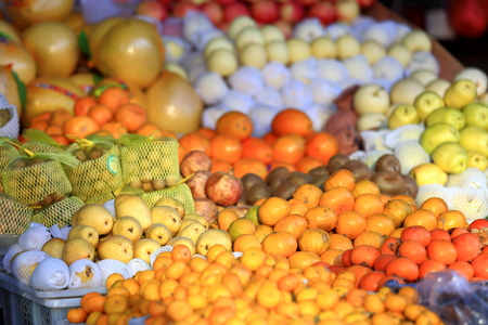 pommegranate: Various fruits -tangerines-oranges-pears-kiwis-pommegranates-apples-grapefruits- in a stall of a market in the lower area. Gyantse city and county-Shigatse pref.-Tibet.