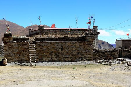 tibetan house: Stone walled peasant house-farm with buddhist prayer flags and red chinese flags on the roof-wooden ladder leaning on wall. Beside the Friendship Highway in Dablung village-Nagarze county-Lhoka or Shannan pref.-Tibet. Stock Photo