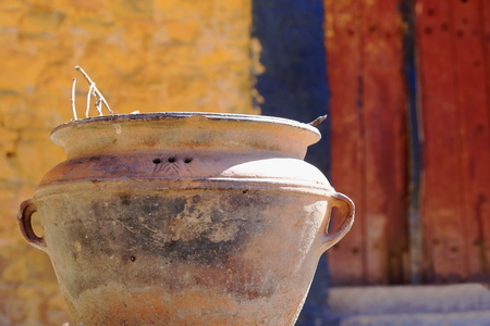 Big terracotta plantpot at the entrance of a yellow painted-red door building. Way down from the main buildings of Drak Yerpa monastery-complex of more than 80 meditation caves. Lhasa pref.-Tibet. photo