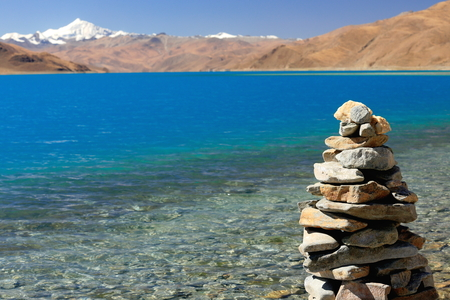 Cairn-stone stack on the shore of the 638 km2-130 km.E'W-70 km.N'S wide-250 long bank-4441 ms.high-turquoise colored Yamdrok Tso-Upper Pasture lake and 7206 ms.high mt.Nojin Kangsang on the background. Lhoka or Shannan pref.-Tibet.