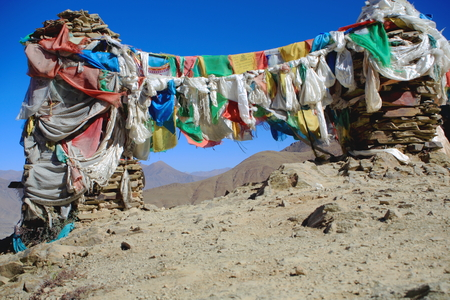 red mountain open space: Five colored buddhist prayer flags hanging from cairns-stacked stones seemingly of slate half way up to the 4793 ms.high Kamba La-pass. Lhoka or Shannan pref.-Tibet.