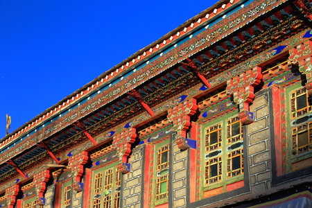 tibetan house: Profusely decorated carved many colored roof eaves of a traditional tibetan house in the lower area of town. Gyantse city and county Shigatse prefecture Tibet.