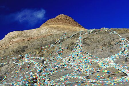 falltime: Buddhist prayer flags hanging from an unidentified peak over the 4200 ms.high Smira Lamountain pass overlooking the turquoise color Manla Reservoir on the Nyang river. Gyantse countyShigatse pref.Tibet.