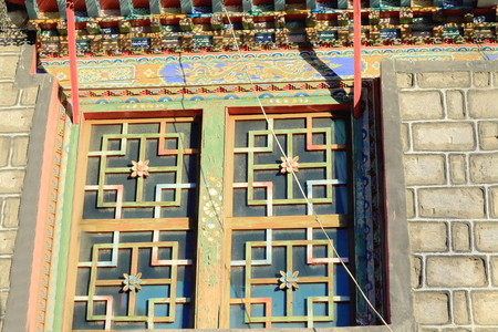 tibetan house: Profusely decorated carved many colored roof eaves and window of a traditional tibetan house in the lower area of town. Gyantse city and county-Shigatse prefecture-Tibet. Stock Photo