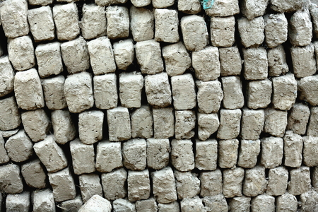 tibetan house: Lots of adobe bricks stacked beside the wall of a traditional tibetan house in the lower area of town at 3977 ms. Gyantse city and county-Shigatse prefecture-Tibet. Stock Photo