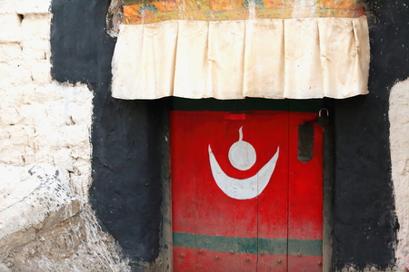 tibetan house: Red painted-traditional tibetan style-wooden door framed in black with strange white symbol under fabric canopy in the old area of the town. Gyantse city and county-Shigatse pref.-Tibet.