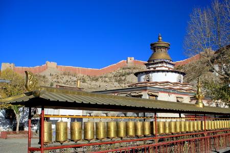 oration: Row of brass prayer wheels inside the Pelkhor Chode-buddhist monastery with the Kumbum or Tashigomang pagoda jutting over.  Stock Photo