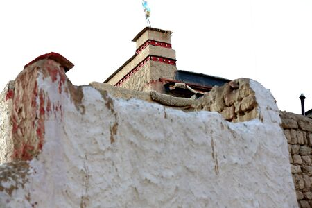 tibetan house: Buddhist prayer flags seen over a white wall  of a townhome in the lower part of the town at 3977 ms.