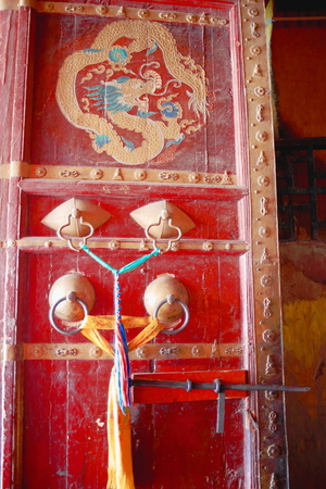 oration: Dust covered-red lacquered-finely decorated wooden door with brass doorknobs and golden Makara picture in the Tsuklakhang temple of the Pelkhor Chode-monast. Stock Photo