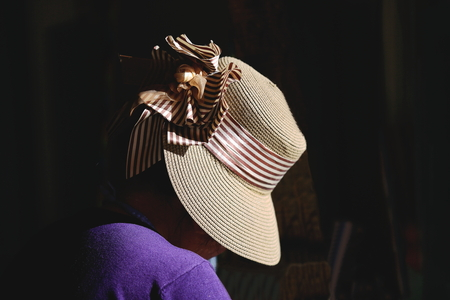 brim: Braided straw hat with white and brown silk band tied in a loop on the head of a tibetan woman wearing a purple cardigan. Shigatse city-county and prefecture at the Yarlung Tsangpo and Nyang Chu rivers confluence. Tibet-China.