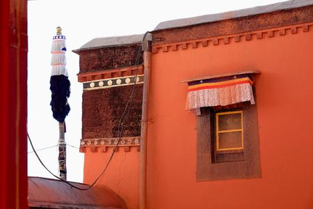 orison: Reddish walls and buddhist flagpole-paint splattered window in the Tashilhunpo-Heap of Glory buddhist monastery seat of Panchen Lama. Shigatse city-county and pref.at the Yarlung Tsangpo and Nyang Chu rivers junction. Tibet-China.