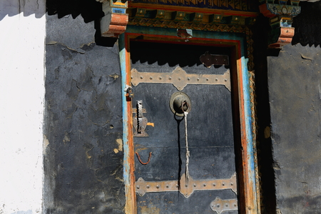 orison: Black wooden door on black painted wall in the Tashilhunpo-Heap of Glory monastery seat of Panchen Lama. The 3840 ms.high Shigatse city-county and pref.at the Yarlung Tsangpo and Nyang Chu rivers junction. Tibet-China.