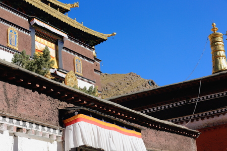 orison: Gilded dhvaja-victory banner and dharmachakra-wheel of law two of the ashtamangala-auspicious symbols on the roof of the Tashilhunpo-Heap of Glory buddhist monastery seat of Panchen Lama. Shigatse city-county and pref.at the Yarlung Tsangpo and Nyang Chu