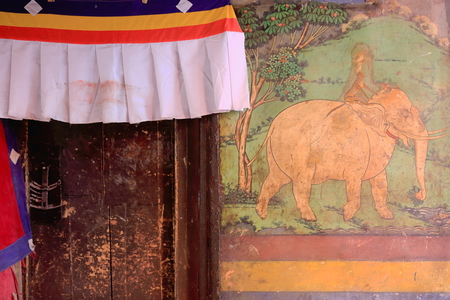 Wooden door under fabric canopy inserted in a decorated wall-interior of building in the Tashilhunpo-Heap of Glory monastery seat of Panchen Lama. Shigatse city-county and pref.at the Yarlung Tsanpo an Nyang Chu rivers junction. Tibet-China.