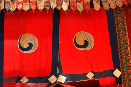 orison: Red curtains with buddhist symbol representing the hub of a dharmachakra-wheel of law. Tashilhunpo-Heap of Glory monastery seat of Panchen Lama in Shigatse city-county and pref.at the Yarlung Tsangpo and Nyang Chu rivers junction. Tibet-China. Editorial