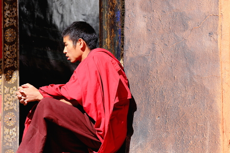 orison: SHIGATSE, TIBET, CHINA-OCTOBER 24: Thoughtful monk sits on the doorjamb and meditates in the Tashilhunpo-Heap of Glory monastery seat of Panchen Lama on October 24, 2012 in the 3840 ms.high Shigatse city-county and pref.at the Yarlung Tsangpo and Nyang Ch Editorial