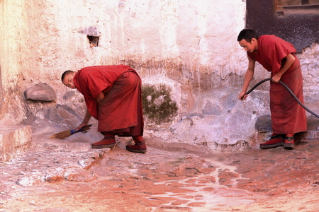 orison: SHIGATSE, TIBET, CHINA-OCTOBER 24: Monks with broom and hosepipe wash the grounds of the Tashilhunpo-Heap of Glory monastery seat of Panchen Lama on October 24, 2012 in the 3840 ms.high Shigatse city-county and pref.at the Yarlung Tsangpo and Nyang Chu ri