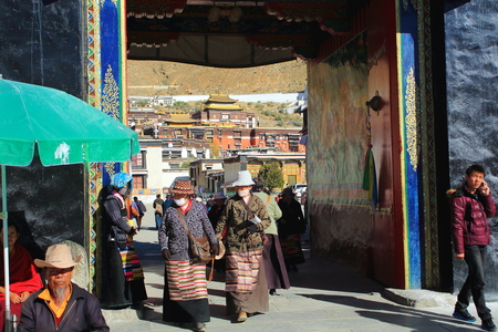 orison: SHIGATSE, TIBET, CHINA-OCTOBER 23: Tibetan devotees pass through the gateway entering and leaving the 1447 AD founded Tashilhunpo-Heap of Glory buddhist monastery-seat of Panchen Lama on October 24, 2012 in Shigatse city-county and pref.at the Yarlung Tsa