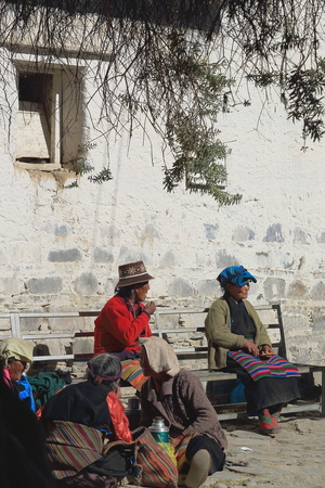 orison: SHIGATSE, TIBET, CHINA-OCTOBER 24: Old tibetan women at chat seat on a bench in the Tashilhunpo-Heap of Glory monastery seat of Panchen Lama on October 24, 2012. Shigatse city-county and pref.-Tibet-China. Editorial