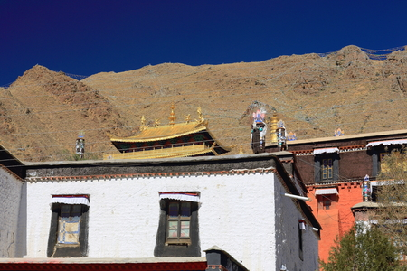 orison: Gilded and fabric covered dhvajas or victory banners-brass lotus flowers-makaras-ashtamangala or auspicious symbols. Roof of Tashilhunpo-Heap of Glory monastery-seat of Panchen Lama. Shigatse-Tibet. Stock Photo