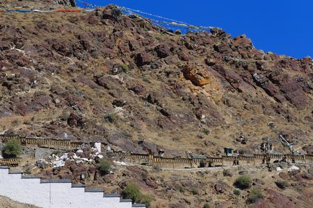 orison: Buddhist prayer flags on the mountain slope and row of buddhist prayer wheels on the outside of the Tashilhunpo-Heap of Glory monastery-seat of Panchen Lama. Shigatse-Yarlung Tsangpo and Nyang Chu rivers junction-Tibet.