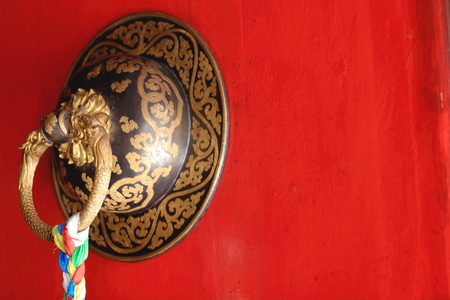 orison: Red door with decorated carved brass doorknob and many colored tassel hanging. Tashilhunpo-Heap of Glory monastery-seat of Panchen Lama in Shigatse-Yarlung Tsangpo and Nyang Chu rivers junction-Tibet.