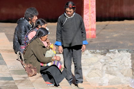 devotee: SHIGATSE, TIBET, CHINA-OCTOBER 24: Devotee family takes a break while visiting Tashilhunpo-Heap of Glory monast.-seat of Panchen Lama on October 24, 2012. Shigatse-Yarlung Tsangpo and Nyang Chu-Tibet.