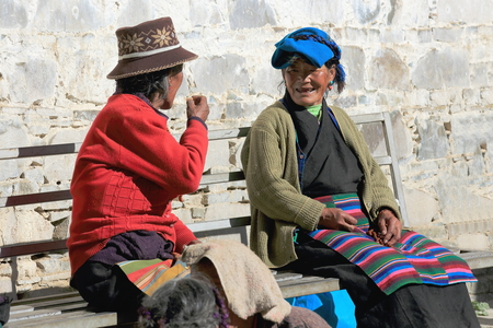 orison: SHIGATSE, TIBET, CHINA-OCTOBER 24: Tibetan old women at chat seat on a bench in the Tashilhunpo-Heap of Glory monastery seat of Panchen Lama on October 24, 2012. Shigatse city-county and pref.-Tibet.