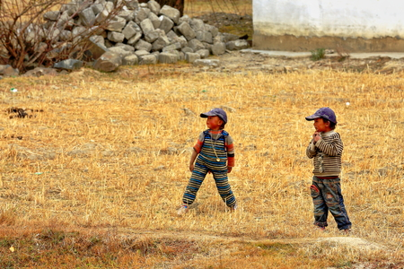 playing with spoon: SHIGATSE, TIBET, CHINA-OCTOBER 24: Tibetan peasant little boys play in a field at their houses.s rear side on October 24, 2012 near Shigatse city-county and pref.-Tibet.