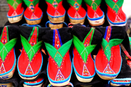many colored: Many colored traditional tibetan fabric shoes for men. Stall of the market in Shigatse city-county and prefecture. Tibet A.R.-China.