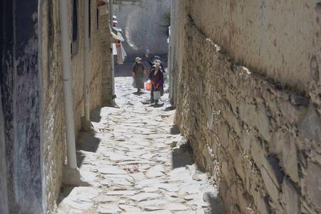 orison: SHIGATSE, TIBET, CHINA-OCTOBER 24: Devotee women whitewash the walls of Tashilhunpo-Heap of Glory monast.-seat of Panchen Lama on October 24, 2012. Shigatse-Yarlung Tsangpo and Nyang Chu rivers-Tibet. Editorial