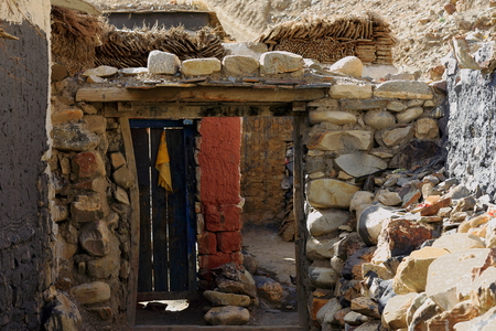 Wooden door open-not very solid stone wall -second wall topped with cowyak dungs-ruins of ancient North Seat of Sakya-Grey Soil monastery on Ponpori Hill-right bank of Chong Chu-river. Sakya-Tibet.
