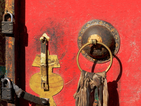 lacquerware: Red lacquered old door of shrine on the grounds of the 1073 AD-Khon Konchog Gyalpo founded North Seat of Sakya monastery-Ponpori Hill on the right bank of Trum or Chong Chu-river. Sakya-Tibet.