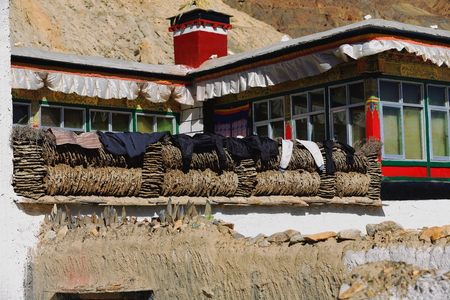 spall: Grey-red-white painted house-laundry along-rows of cow and yak dung. Grounds of the 1073 AD-Khon Konchog built Sakya-Grey Soil monast. Ponpori Hill on right bank of Trum or Chong Chu river-Sakya-Tibet