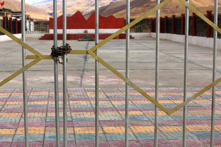padlocked: Public square closed by padlocked grate-foot of Bonbori Hill-Trum or Chong Chu river right bank-grounds of the 1073 AD-Khon Konchog Gyalpo founded North Seat of Sakya-Grey Soil monastery. Sakya-Tibet. Stock Photo
