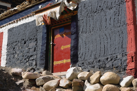 lintel: Grey-red-white painted house with red door. Grounds of the 1073 AD-Khon Konchog founded North Seat of Sakya-Grey Soil monast. Slope of Ponpori Hill-right bank of Trum or Chong Chu-river. Sakya-Tibet.