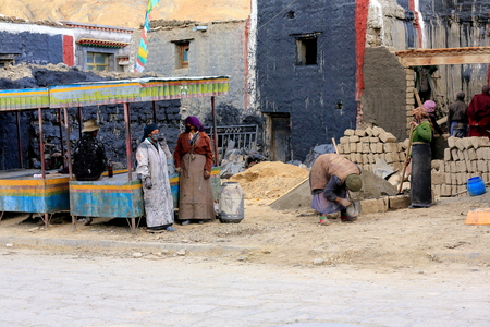 adobe wall: SAKYA, TIBET, CHINA-OCTOBER 25: Monks and locals get ready for community service: the painting of the walls facing the Sakya-Grey Soil monasterys South Seat on October 25, 2012. Sakya-Tibet. Editorial