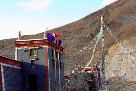 flag pole: Big prayer flag pole at the eastern entrance to the South Seat of Sakya-Grey Soil monastery. Dhvajas and buddhist-chinese flags on rooftop. Sakya-Shigatse prefecture-Tibet.