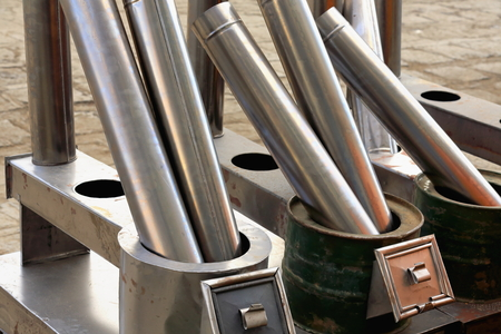stove pipe: Stainless steel exhaust tubes and stoves for sale on the outside of a shop in Sakya-Grey Soil town and tibetan monastery on the Trum or Chong Chu river left bank. Sakya-Tibet.