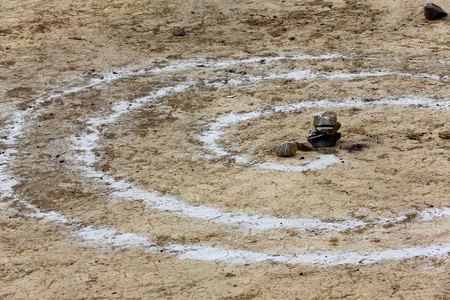 field crop: White dust-marked spiral drawing-floor of Trum or Chong Chu river right bank-foot of Bonbori Hill on grounds of the 1073 AD-Khon Konchog Gyalpo built North Seat of Sakya-Grey Soil monast. Sakya-Tibet. Stock Photo