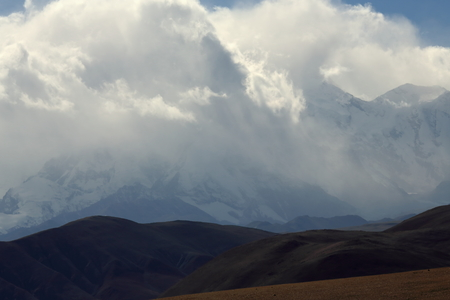 mounts: Clouds cover mounts Shisha Pangma-Gosainthan-Crest above the grassy plains 8013 ms.Yebokangal Ri 7365 ms.to the right. From Tong La pass at 5120 ms.-Friendship Highway between Tingri and Nyalam-Tibet