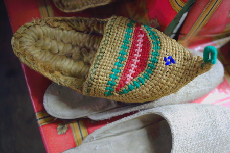 slew: Traditional nepalese hempen slippers for sale in the windowshop of a souvenir store in the Thamel area of Kathmandu city. Kathmandu district-Bagmati zone-Nepal. Stock Photo