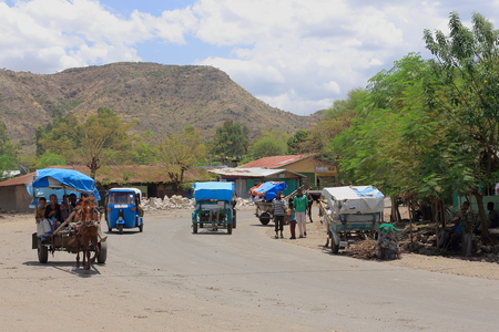 autorick: DEBRE BIRHAN, ETHIOPIA-MARCH 24: Horse carts and auto ricks transport local people-kids back from school down the main street on March 24, 2013. Debre Birhan town-S.N.Shewa zone-Amhara region-Ethiopia.