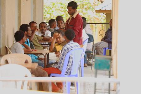 gather: DEBRE BIRHAN, ETHIOPIA-MARCH 24: Local men gather on the porch of a bar beside the road-waiter serving them on March 24, 2013. Debre Birhan-Semien Shewa zone-Amhara region-Ethiopia.