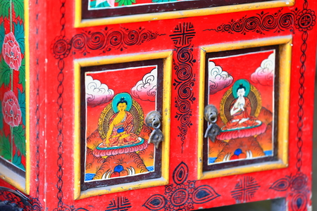 lacquer ware: Nepalese-tibetan buddhist style furniture: red lacquered wooden ark showing images of the Buddha for sale in a souvenir shop of the Thamel area-Kathmandu. Kathmandu district-Bagmati zone-Nepal-Asia