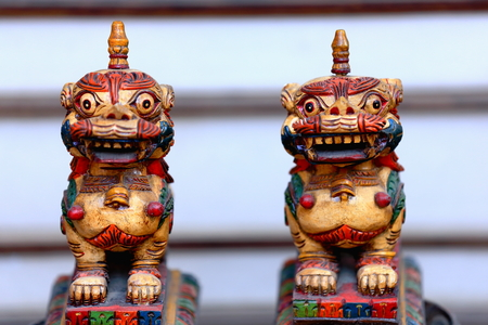 shop for animals: Traditional nepalese wooden carved snow lion figurines for sale in the windowshop of a souvenir store in the Thamel area-Kathmandu. Kathmandu district-Bagmati zone-Nepal. Stock Photo