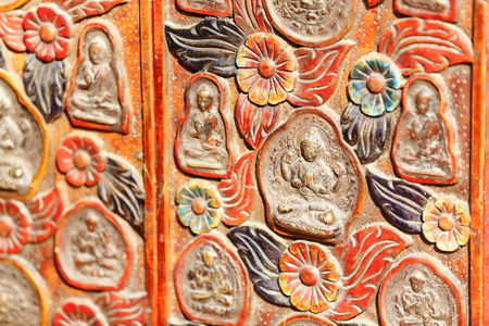 exhibiting: Traditional nepalese woodcarved folding screen exhibiting buddhist decoration for sale in the windowshop of a souvenir store in the Thamel area-Kathmandu. Kathmandu district-Bagmati zone-Nepal. Stock Photo