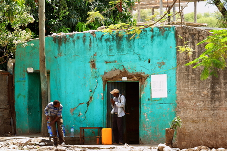 filling in: DEBRE BIRHAN, ETHIOPIA-MARCH 24: Two local men-one with hand saw on shoulder chat in the street wile filling in water bottles on March 24, 2013. Debre Birhan-Amhara region-Ethiopia.