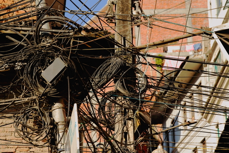 utility pole: Utility pole and incredible tangle of electric cables with insulators in the middle of a street in the Thamel area-Kathmandu. Kathmandu district-Bagmati zone-Nepal. Stock Photo